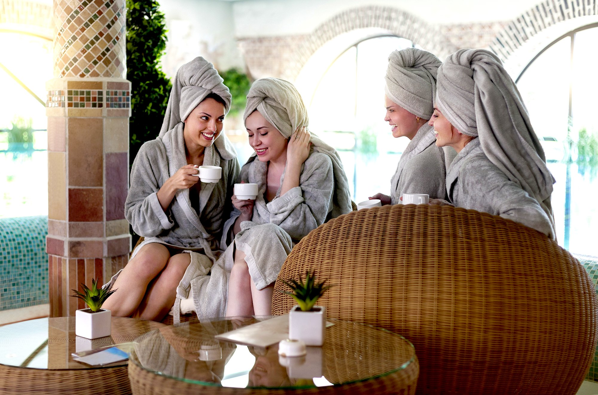 Four young women drinking tea at spa resort
